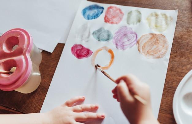 Vue de dessus des mains et de la peinture au pinceau gouache aquarelle
