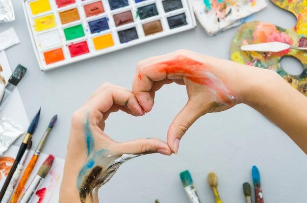Vue de dessus des mains sales faisant un coeur avec du matériel de peinture