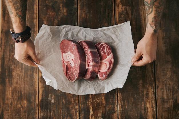 Vue de dessus des mains tatouées tiennent du papier kraft blanc avec trois grands steaks de jambe crus avec de l'os dessus, tout sur la vieille table en bois brossé