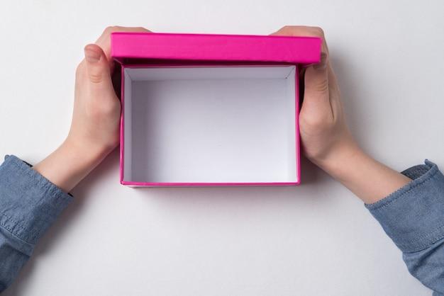 Vue de dessus des mains tenant une boîte en carton rose sur fond blanc.