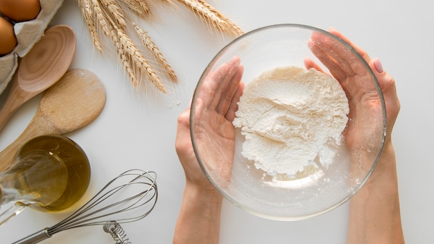 Vue de dessus mains tenant un bol avec de la farine