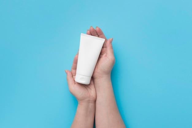 Vue de dessus des mains tenant une bouteille de gel hydroalcoolique