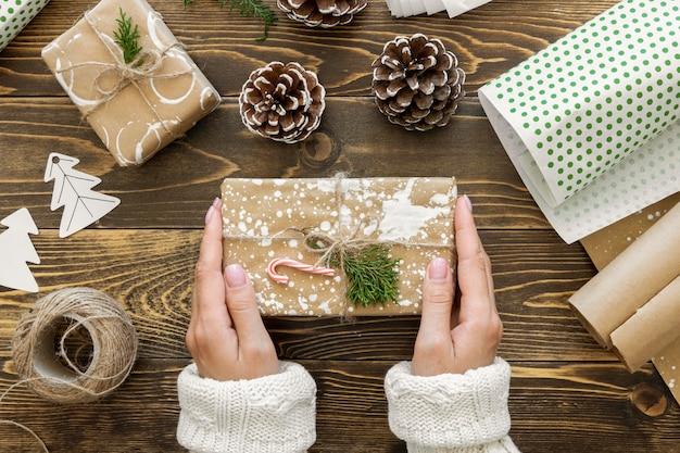 Vue de dessus des mains tenant le cadeau de noël avec de la ficelle et des pommes de pin