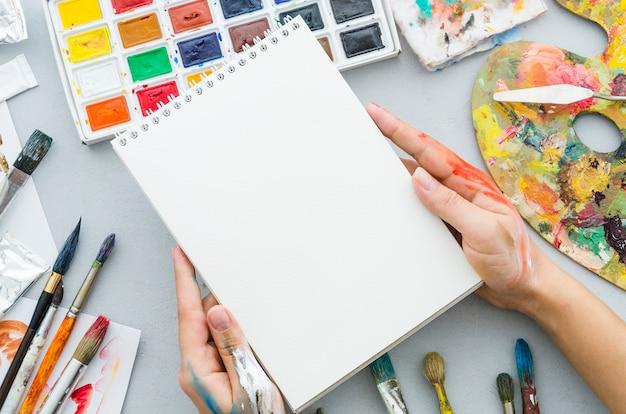 Vue de dessus mains tenant un cahier entouré d'éléments de peinture