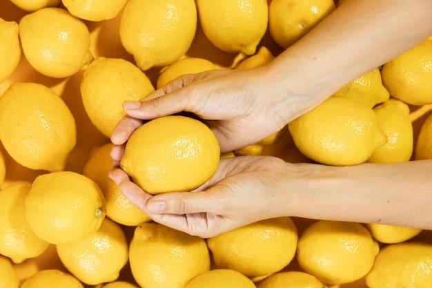 Vue de dessus mains tenant citron brut