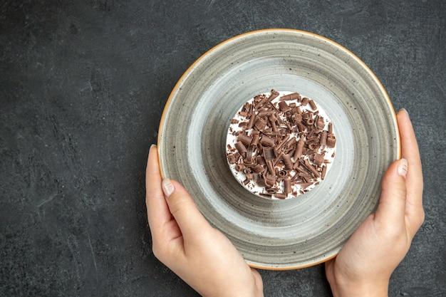 Vue de dessus des mains tenant un délicieux petit gâteau crémeux fait maison