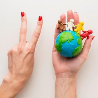 Vue de dessus des mains tenant le globe en pâte à modeler et les gens et faisant signe de paix