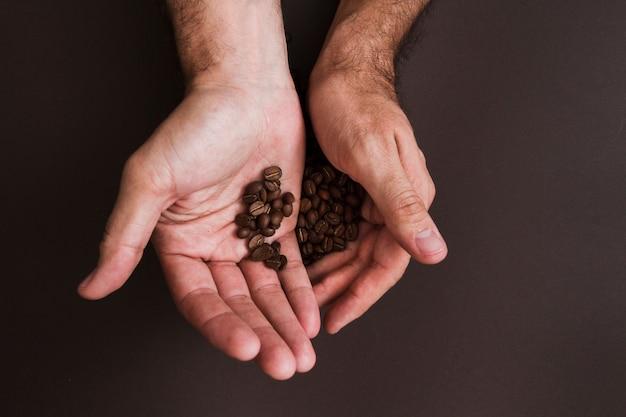 Vue de dessus des mains tenant des grains de café