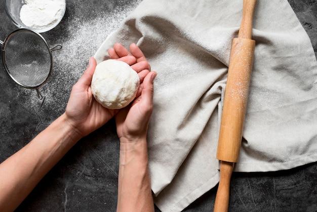 Vue de dessus mains tenant la pâte près du rouleau à pâtisserie