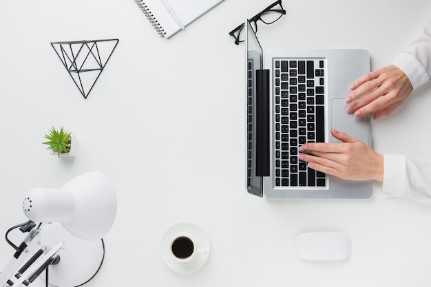 Vue de dessus des mains travaillant sur ordinateur portable sur le bureau