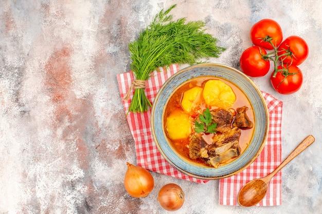 Vue de dessus maison soupe bozbash serviette de cuisine un tas de tomates à l'aneth oignons cuillère en bois sur une surface nue