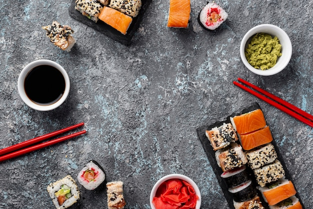 Vue dessus, maki sushi, baguettes, cadre, sauce soja