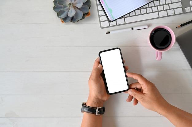 Vue de dessus mâle main tenant accessoires de bureau et téléphone intelligent mobile écran blanc