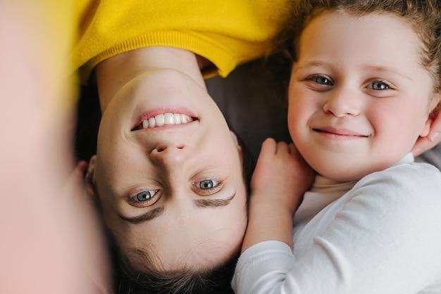 Vue de dessus de maman et petite fille enfant se détendre dans une chambre confortable. maman joyeuse et petite fille couchée ensemble sur la literie lit souriant regardant la caméra se sent joyeuse, faisant des photos de selfie heureux