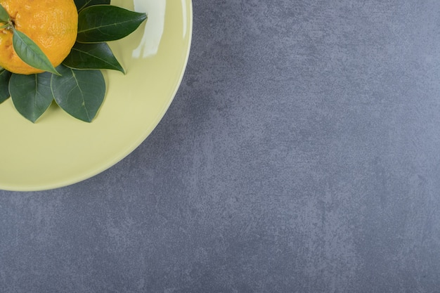 Vue de dessus de la mandarine fraîche et des feuilles sur plaque jaune.