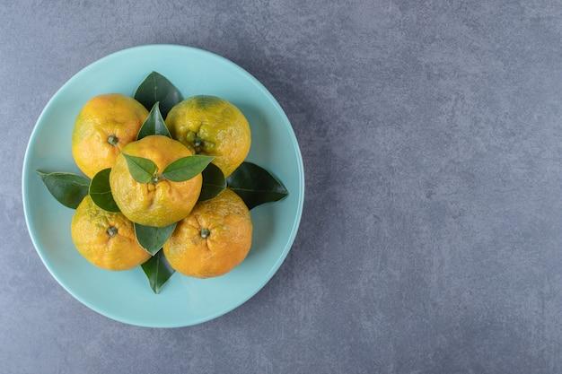 Vue de dessus des mandarines biologiques fraîches sur plaque bleue.
