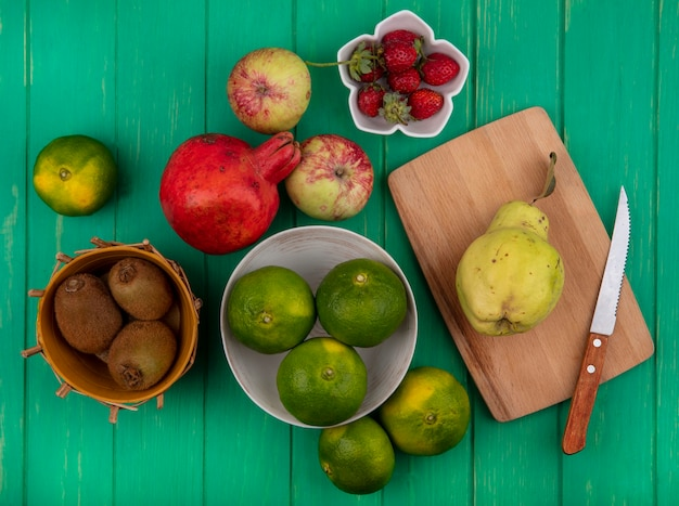 Vue de dessus des mandarines dans un bol avec des pommes kiwi grenade et poire sur une planche à découper