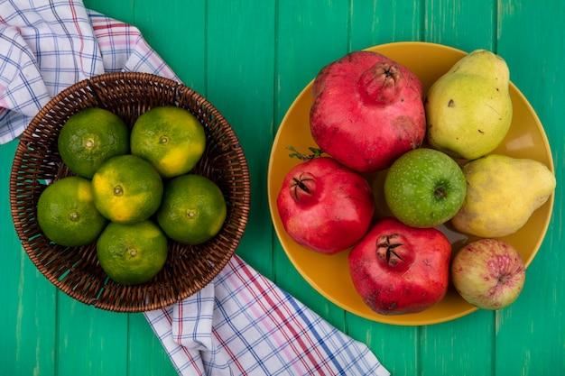 Vue de dessus des mandarines dans un panier avec des pommes et des poires grenades sur une assiette sur un mur végétal
