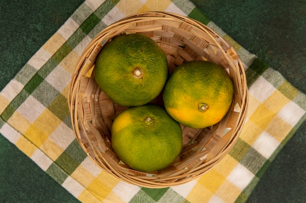 Vue de dessus des mandarines dans un panier sur une serviette à carreaux jaune-vert