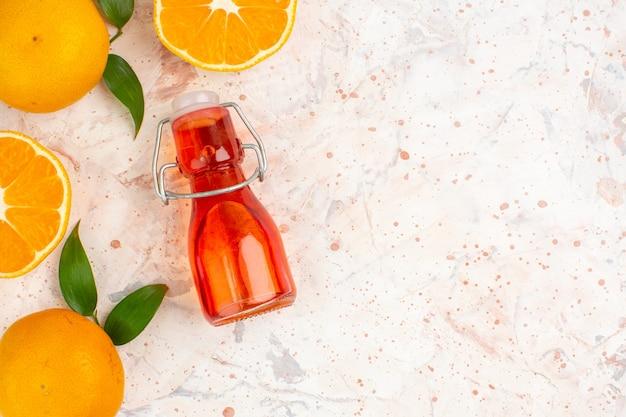 Vue de dessus mandarines fraîches coupées de mandarines petite bouteille sur une surface isolée lumineuse avec espace libre