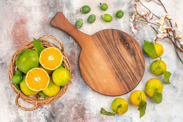 Vue de dessus des mandarines fraîches dans un panier en osier une planche à découper des mandarines feykhoas sur fond nu