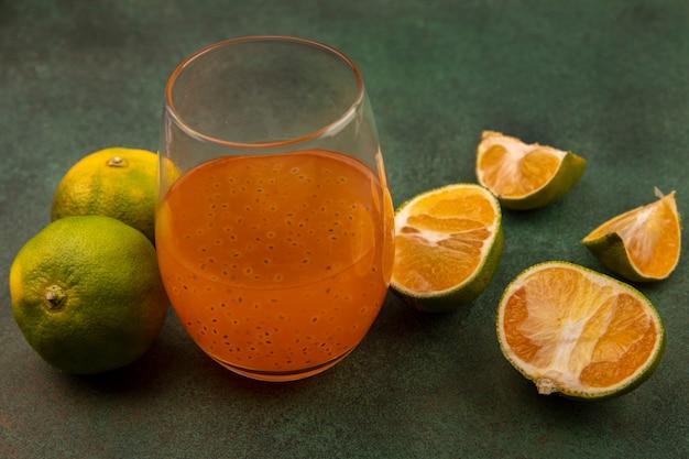 Vue de dessus des mandarines fraîches avec du jus de fruits frais dans un verre