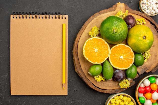 Vue de dessus des mandarines fraîches avec feijoa et bonbons sur fond noir
