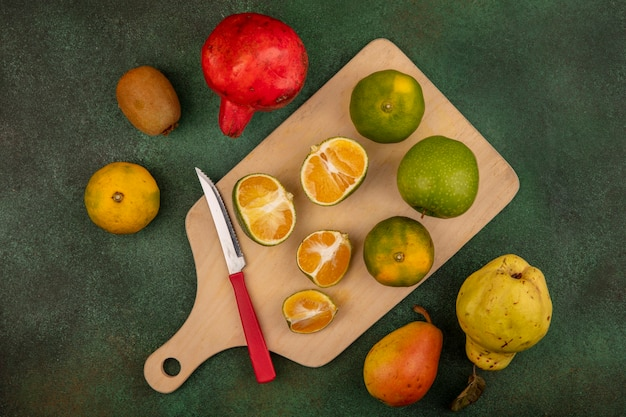 Vue de dessus des mandarines fraîches sur une planche de cuisine en bois avec un couteau avec de délicieux fruits tels que la grenade poire