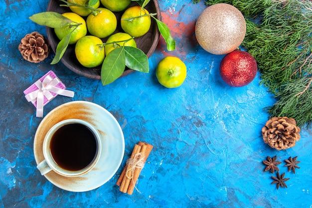 Vue de dessus mandarines jaunes avec des feuilles dans un bol en bois bâtons de cannelle anis sur surface bleue espace libre