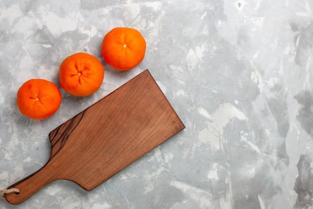 Vue de dessus des mandarines orange fraîches entières d'agrumes aigres et moelleux sur un bureau blanc clair.