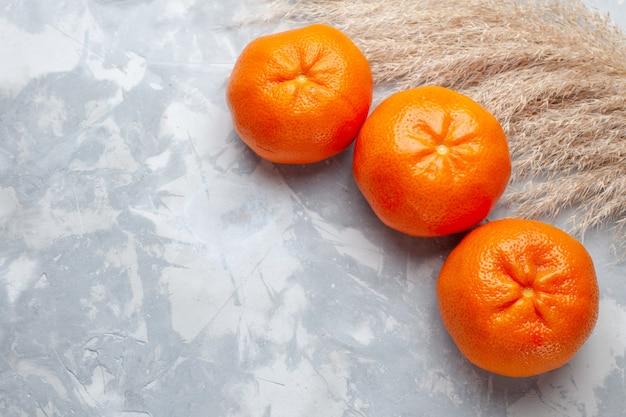Vue de dessus des mandarines orange fraîches entières moelleuses juteuses sur le bureau blanc vitamines de couleur exotique d'agrumes