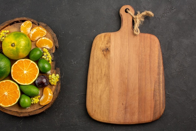 Vue de dessus des mandarines vertes fraîches avec des feijoas sur une table sombre