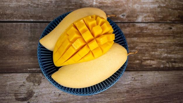 Vue de dessus de la mangue mûre coupée en dés fraîche et belle dans une assiette en céramique bleue avec fond en bois