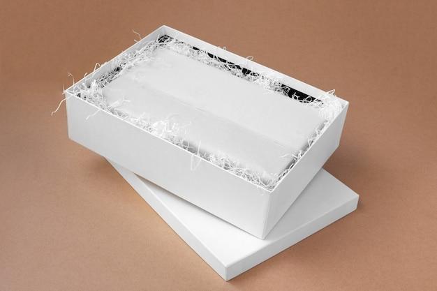 Vue de dessus maquette d'une boîte ouverte blanche avec des vêtements dans un papier de soie blanc vierge et propre et du papier déchiqueté pour la protection