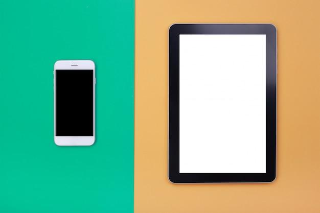 Vue de dessus maquette tablette et smartphone sur fond pastel vert et orange