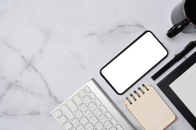 Vue de dessus maquette téléphone intelligent, bloc-notes, clavier et tasse à café sur fond de marbre