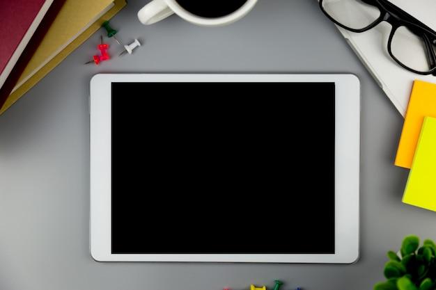 Vue de dessus avec une maquette vierge tablette sur l'espace de travail de bureau.