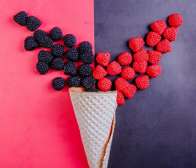 Vue de dessus de la marmelade sous forme de framboises sur fond noir et mûres sur fond rouge avec un cornet gaufré