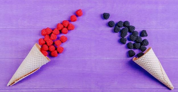 Vue de dessus de la marmelade sous forme de framboises et mûres avec des cornets gaufres sur fond violet