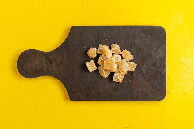 Vue de dessus de la marmelade en tranches sucrée et du sucre sur une surface jaune