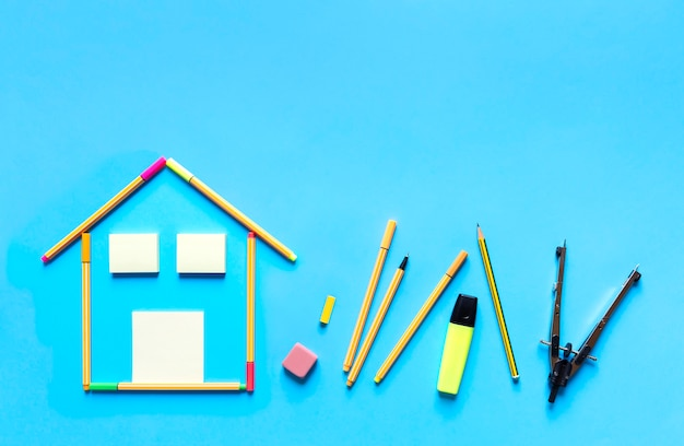 Vue de dessus des marqueurs fluorescents formant un dessin d'une maison et d'autres articles de papeterie sur fond bleu pastel.