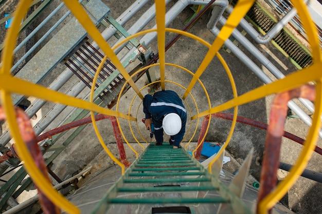 Vue de dessus masculine monter l'huile de réservoir d'inspection visuelle de stockage d'échelle d'escalier