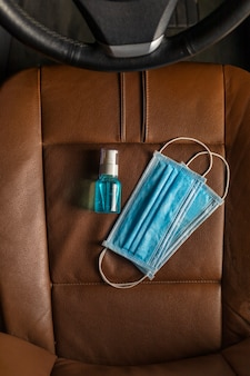 Vue de dessus masque médical alcool gel désinfectant pour les mains sur le siège auto.