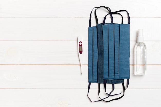 Vue de dessus des masques en coton faits à la main, thermomètre numérique et désinfectant au gel d'alcool sur fond de bois. concept d'équipement de protection avec espace copie