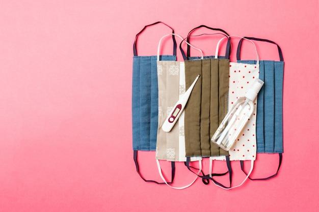 Vue de dessus des masques de coton faits maison, thermomètre numérique et désinfectant pour les mains à l'alcool sur fond rose. concept de soins de santé avec espace copie