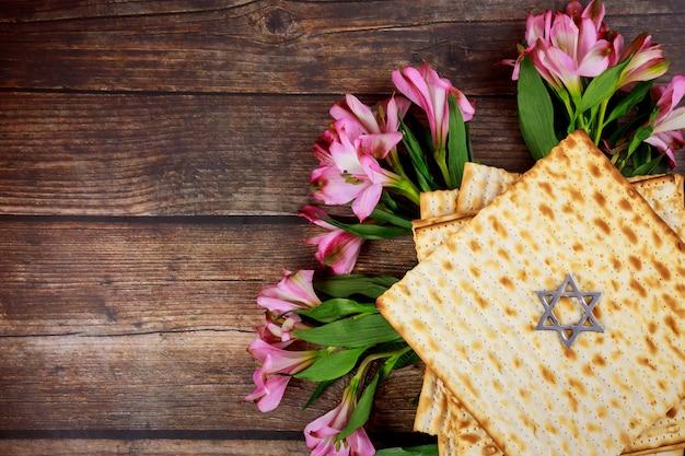 Vue de dessus de la matsa et des fleurs roses. fête juive de la pâque.
