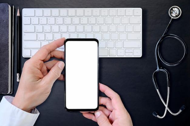 Vue de dessus médecin main tenant le smartphone avec écran blanc