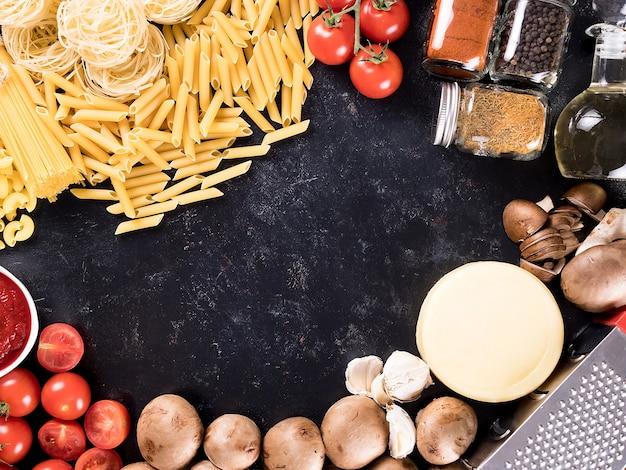 Vue de dessus mélange de pâtes crues non cuites, spaghettis, macaronis à côté de champignons, fromage, sauce tomate, tomates fraîches, épices et huile de tournesol. espace de copie disponible