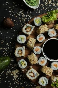 Vue de dessus mélanger des rouleaux avec de la sauce soja sur un support avec des graines de sésame, du riz au gingembre et du wasabi