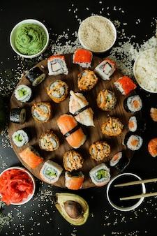 Vue de dessus mélanger rouleaux sur un support avec sauce soja sauce wasabi gingembre avocat et graines de sésame